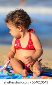 Baby girl on the beach seated on a towel