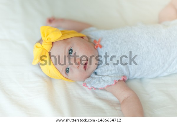 Baby girl on bed looking at camera