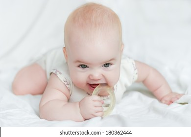 Baby girl on her stomach with teether in the mouth