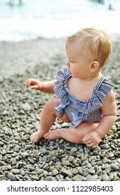 baby girl on the pebble  beach playing with stones