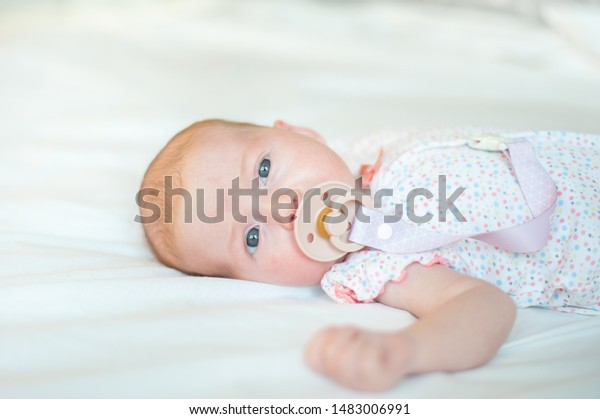 Baby girl on white bed with pacifier