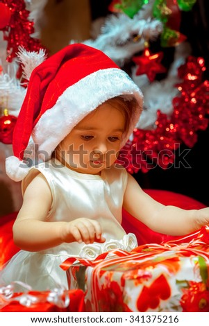 baby girl opens her first christmas gift new year christmas mood