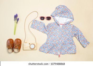 Baby girl outfit, top view, floral spring jacket, shoes and wooden camera toy