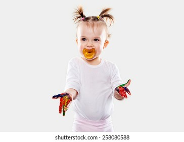 the baby girl with a pacifier in gouache soiled hands and shirt isolated on the white background
