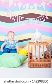 baby girl with pigeons on cage