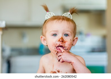 Baby girl with pigtails celebrating her first birthday with a messy chocolate cake. Photos taken inside a home in Reno, Nevada, USA using natural window.