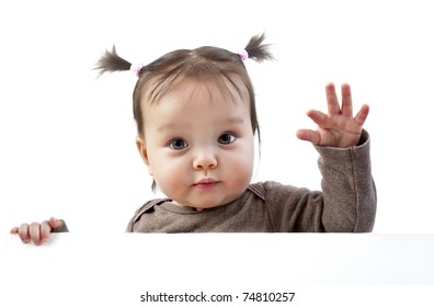 Baby girl with pigtails waving hand above white banner