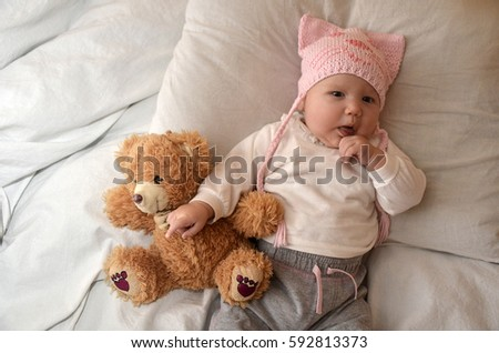 0a5a4c94227 baby girl in pink hat and teddy bear in his bloodstream on a blanket