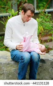 Baby girl in pink overalls lies on the father's lap outdoor