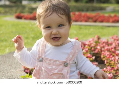 Baby girl in pink is sitting on green meadow and play with flowers