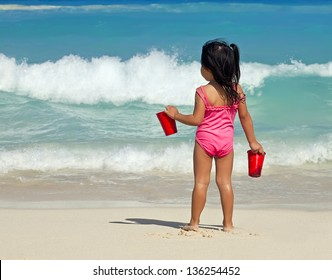baby girl in a pink swimsuit near the sea