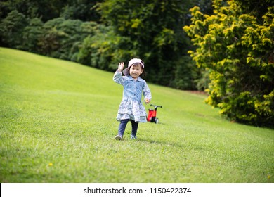 baby girl play bike in Summer forest park