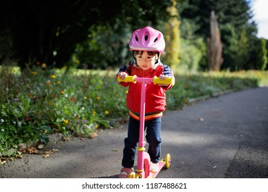 baby girl play scooter in forest park