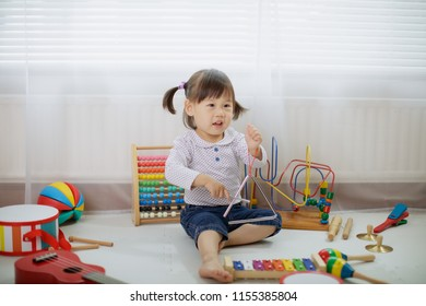 baby girl play triangle at home