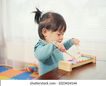 baby girl play xylophone at home