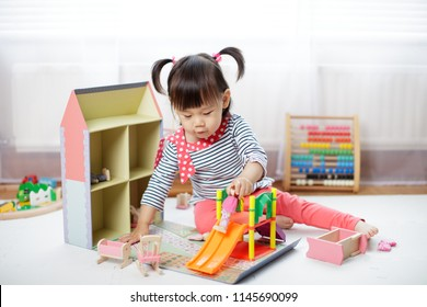 baby girl playing doll house at home
