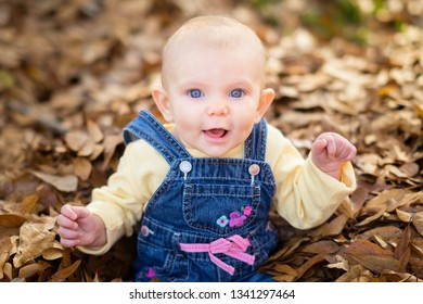 Baby girl playing in leaves