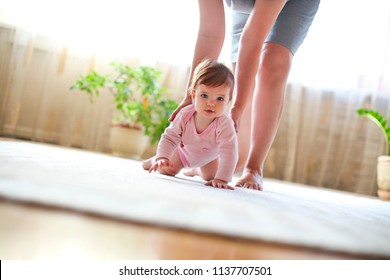 Baby girl playing with mother in the room