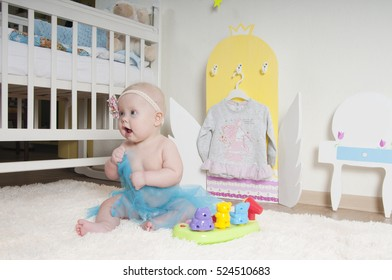 Baby girl playing on the carpet at home or kindergarten