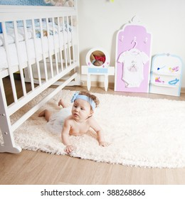 Baby girl playing on a fur rug in the nursery