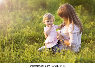 Baby girl playing on a meadow with her mother talking to her