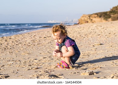 Baby girl playing on the sand beach