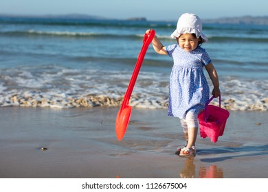 baby girl playing on summer beach