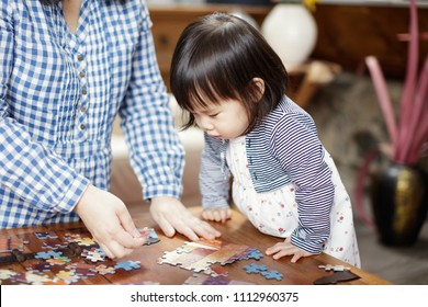 baby girl playing puzzle with Mom