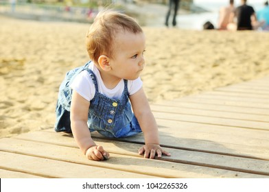 baby girl playing sand on the beach
