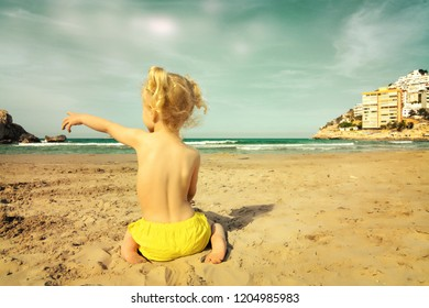 Baby girl playing in the sand on the beach