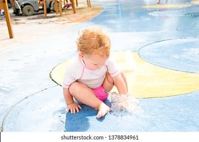 baby girl playing in water on splash pad
