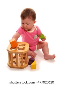 Baby girl playing with wooden shape sorter cutout