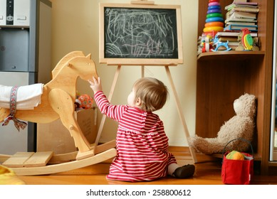 Baby girl playing with a wooden toy horse