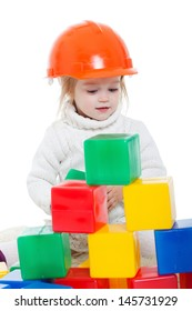 Baby girl plays with toy blocks over white background