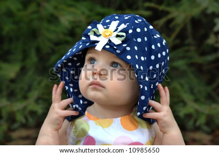 e64ec7afc1f Baby girl poses with a floppy hat. Hat is navy with white polka dots.
