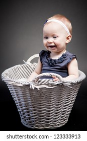 Baby girl posing in a vintage basket. The look at her face expresses her exploration of the world.