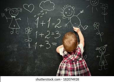 baby girl pupil draws a chalk on a blackboard