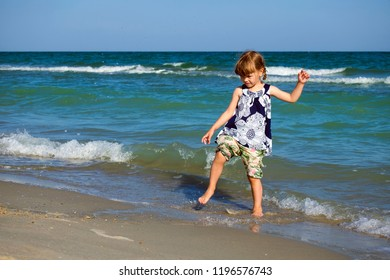 Baby girl raging on the sea beach smashing the water down