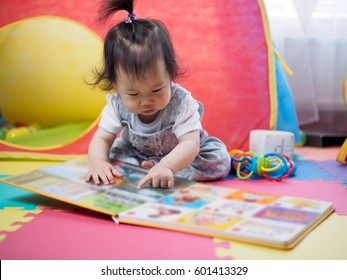 baby girl reading book at home