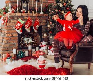 Baby girl in red dress and mother near Christmas tree