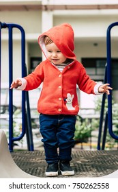 Baby girl in red knitted hoodie and jeans walking on a playground in the city