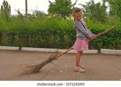 Baby girl riding the broom.