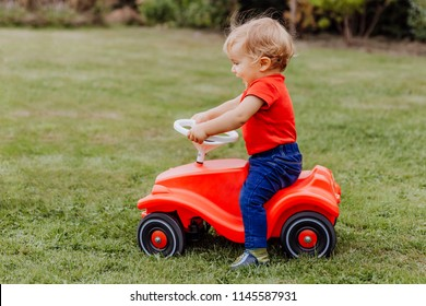 Baby girl riding toy car in garden – Kempen, Germany
