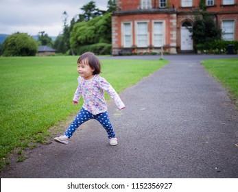 baby girl running in Summer forest park