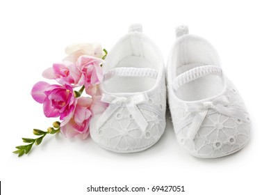 Baby girl shoes with pink flowers isolated on white background