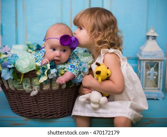 baby girl sisters kissing on blue wooden background