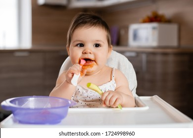 Baby girl sits in a child's chair eating vegetable puree. Mom feeds baby