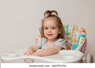 baby girl sitting in a child's chair eating fruit on a white background. baby food concept, space for text