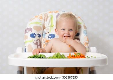Baby girl sitting in a highchair eating raw, seasonal vegetables: carrots, beans, peas, celery