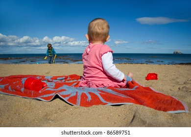 Baby girl sitting on a beach towel looking out to sea while her brother plays in the sand